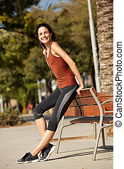 Full length happy sports woman relaxing outdoors