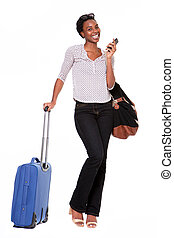 Full length happy woman standing with suitcase and cellphone on white background
