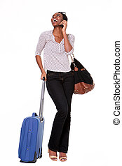 Full length happy woman standing with suitcase and smart phone on isolated white background