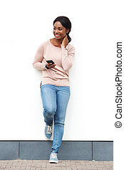 Full length happy young african american woman standing against white wall with cellphone