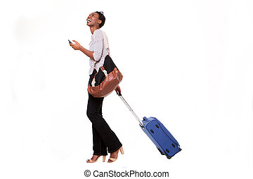 Full length happy young african american woman walking with luggage and smart phone on isolated white background
