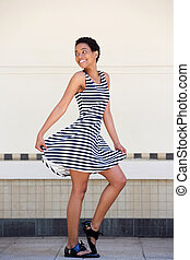 Full length happy young black woman in striped dress