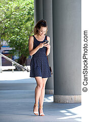 Full length happy young woman walking in city with cellphone