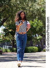 Full length happy young woman walking outside with mobile phone