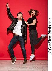 Full length image of carefree screaming punk couple posing