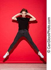 Full length image of cheerful punk woman jumping
