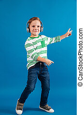 Full length image of cheerful young boy listening music