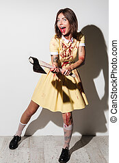 Full length image of crazy zombie woman in dress attacking