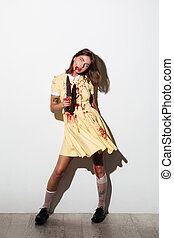 Full-length image of crazy zombie woman in dress with knife