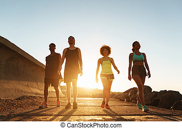 Full length image of fitness people walking outdoors