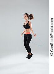 Full length image of fitness woman jumping with skipping rope