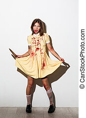 Full length image of frightening zombie woman in dress