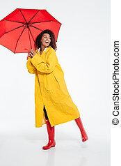 Full length image of Happy african woman in raincoat posing
