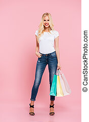 Full length image of happy blonde woman posing with packages