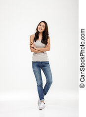 Full length image of Happy brunette woman posing with crossed arms