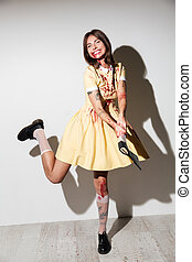 Full length image of happy zombie woman in dress attacking