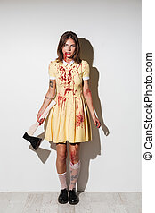 Full length image of mad zombie woman posing with axe