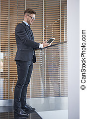 Full length image of man with digital tablet