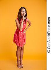 Full length image of Mystery brunette woman in dress