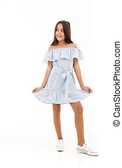 Full length image of Playful young brunette girl in dress