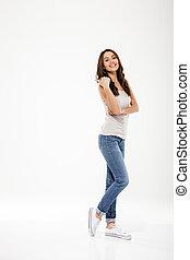 Full length image of Pleased brunette woman posing sideways