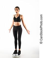 Full length image of Shocked curly brunette fitness woman