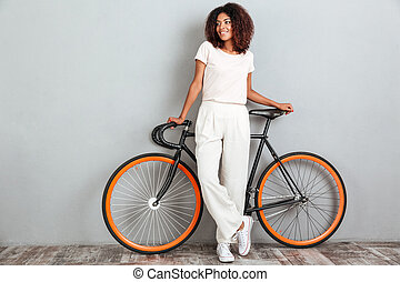 Full length image of Smiling african woman posing with bicycle