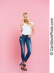 Full length image of smiling blonde woman posing