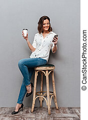 Full length image of Smiling woman posing on chair