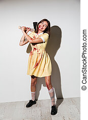 Full length image of smiling zombie woman in dress attacking