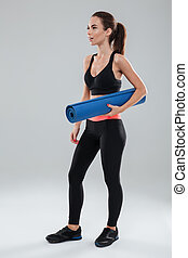 Full length image of surprised fitness woman with fitness mat