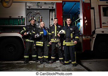 Full-length image of three fire men and woman on background of fire truck