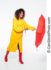 Full-length image of young african woman in raincoat opening umbrella