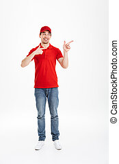 Full length image of young courier in red uniform presenting copyspace text or product with pointing fingers aside and smiling broadly, isolated over white background