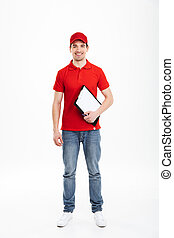 Full length image of young courier man 20s in red uniform and jeans looking on camera and holding clipboard, isolated over white background
