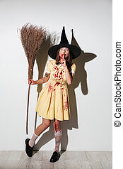 Full length image of young woman in halloween costume