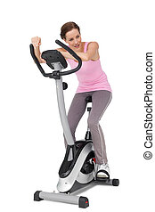 Full length of a beautiful woman on stationary bike