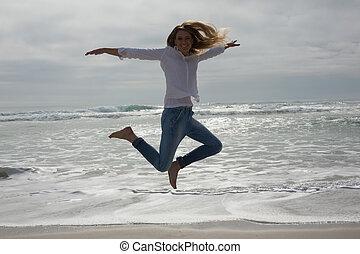Full length of a casual woman jumping at beach