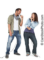 Full length of a couple singing int - Full length of a young...