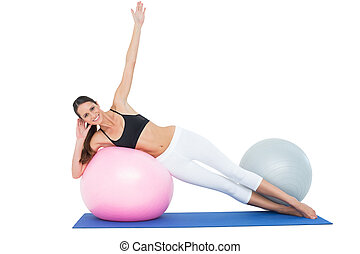 Full length of a fit young woman stretching on fitness ball