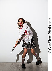 Full length of a mad zombie woman holding an axe