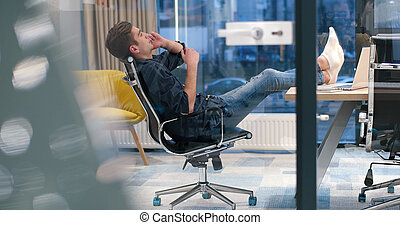 businessman sitting with legs on desk
