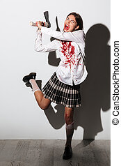 Full length of a scary mad zombie woman holding an axe