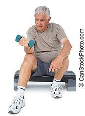 Full length of a senior man exercising with dumbbell