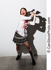 Full length of a smiling mad zombie woman holding an axe