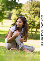 Full length of a smiling woman sitting on grass in park