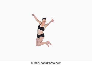 Full length of a sporty young woman jumping