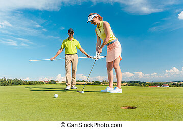 Full length of a woman playing professional golf with her male m