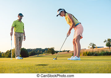 Full length of a woman playing professional golf with her male partner