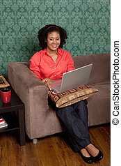 Full length of a young African American using laptop at home